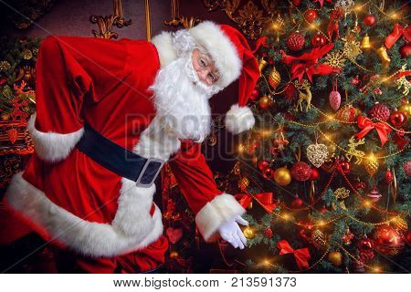 Santa Claus next to a beautiful ornate Christmas tree. Santa Claus dress up the Christmas tree.