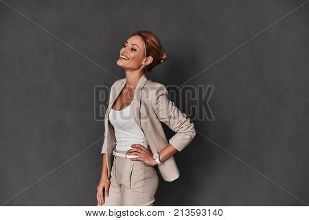 Young expertise. Attractive young woman in smart casual wear keeping hand on hip and smiling while standing against grey background