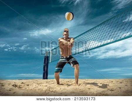 Beach volleyball player in action at sunny day under blue sky.