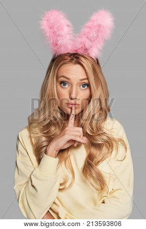 What to do? Confused young woman in pink bunny ears keeping index finger on her lips while standing against grey background