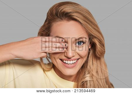 Take your chance! Attractive young smiling woman covering eye with hand and looking at camera while standing against grey background