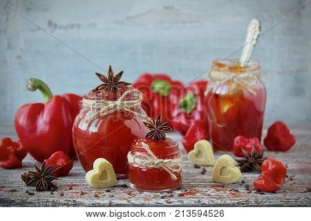 Sweet bell pepper and chili pepper jam in a glass jar and fresh sweet and hot peppers on wooden background