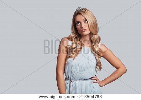 Feeling uncertain. Prideful young woman in crown keeping hand on hip and looking away while standing against grey background
