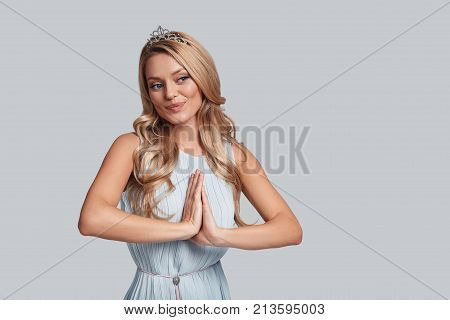 Fairy princess. Beautiful young woman keeping hands clasped and smiling while standing against grey background