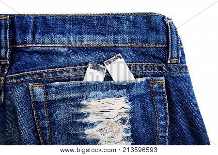 Chewing two gums in the jeans pocket of denim pants. Close-up