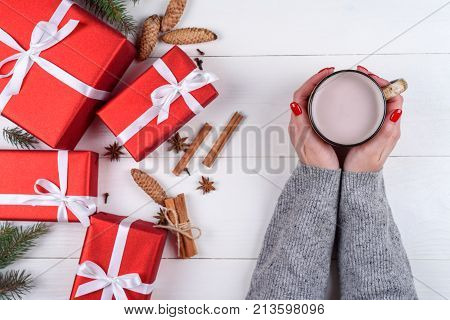 Cup of hot cocoa or chocolate in girl hands with red manicure. Flat lay top view. Young woman in sweater with cacao mug. Christmas gifts on wooden background. Sweet winter times. Traditional drink