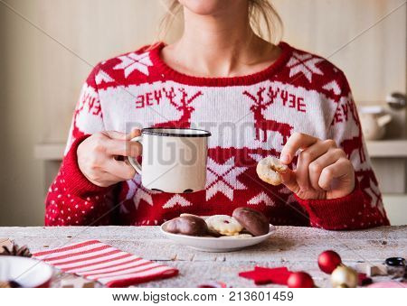 Christmas composition on a vintage wooden background. Unrecognizable woman eating biscuits and drinking coffee.