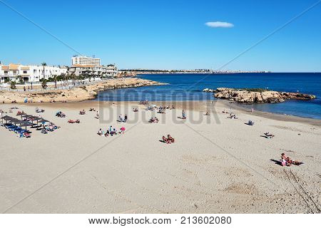 Orihuela Spain - November 5 2017: People sunbathing at the Cala Capitan beach in the Cabo Roig popular place for holidaymakers. Province of Alicante. Costa Blanca. Spain