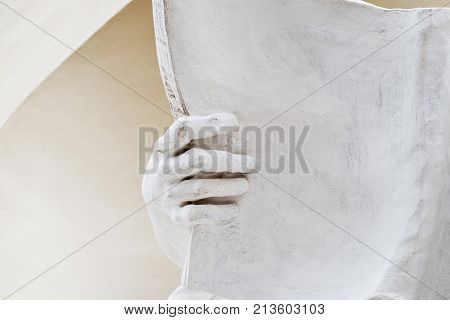 stone statue detail of human hand holding huge opend book