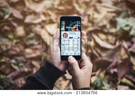 Chiang Mai Thailand Nov 102017: Man hand holding iphone 6s with social Internet service Pinterest on the screen. Pinterest is an online pinboard that allows people to pin their interesting things.