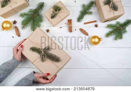 Christmas gift wrapping background copy space. Female hands holding christmas present box wrapped in kraft top view. Winter holidays concept flat lay. Woman with red manicure packing Christmas gift