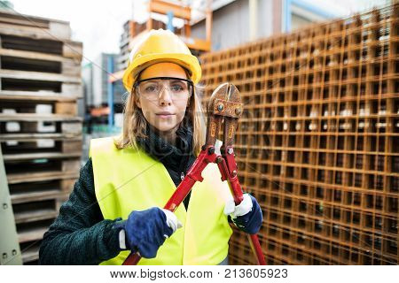 Female worker with bolt cutters in an industrial area. Beautiful young woman working outside a warehouse building.