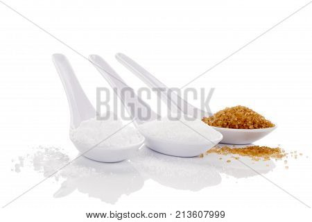 Various types of sugar brown white and powdered sugar on spoons isolated on white background. Unhealthy eating.