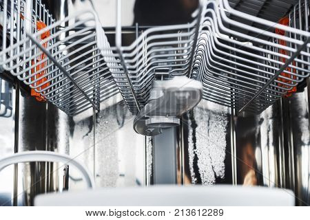 Dishwasher mana machine after washing dishes from the inside. Upper carriage and basket of dishwasher