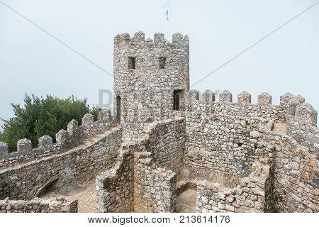 View of ruin Moorish Castle (Castelo dos Mouros) in fog. Sintra Portugal