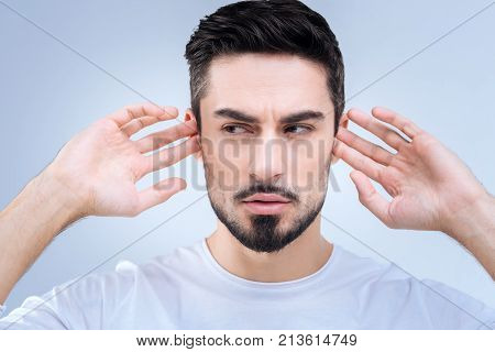 Unnecessary information. Stubborn clever young man looking aside while closing his ears with fingers and rejecting to listen to a boring person and perceive unnecessary information