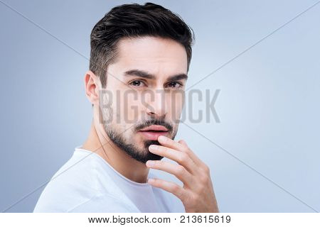Tender touch. Romantic pleasant sensitive man looking emotional while touching his lips and thinking about a sweet kiss of his beloved woman