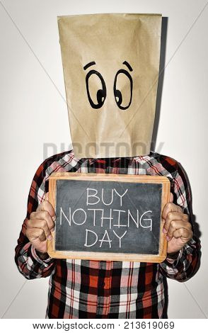 a young man wearing casual clothing with a paper bag in his head with a pair of eyes drawn in it shows a chalkboard with the text buy nothing day written in it