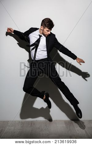 Full length photo of handsome caucasian man in black suit flying over white background