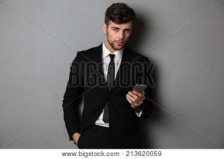 Young confident businnesman with hand in his pocket holding mobile phone, looking at camera, isolated on gray background