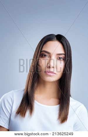 Strict woman. Young elegant beautiful woman making an impression of a strict angry person while standing calmly and looking into the distance