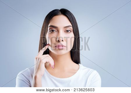 Strict employer. Young professional smart businesswoman looking strict and serious while standing against the blue background and listening to the workers of her company
