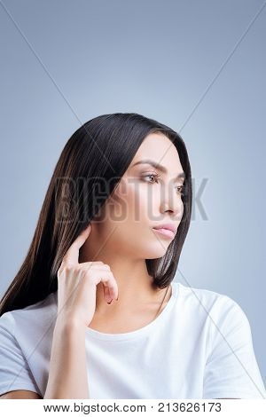 So boring. Beautiful calm young woman feeling bored and tired while touching her neck with a finger and watching a dull documentary film