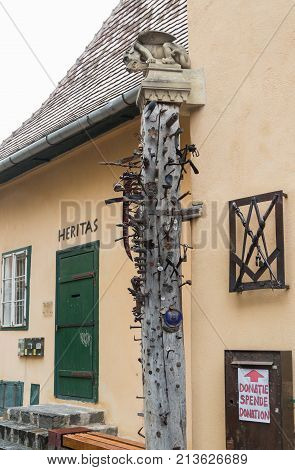 Sibiu Romania October 07 2017 : A pillar standing next to the smithy decorated with gargoyles and studded with various forging items in Sibiu city in Romania