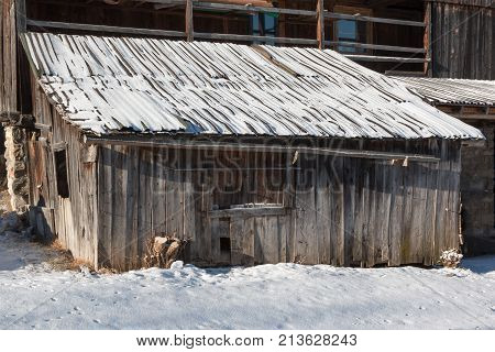 Wooden Shack In Winter Day With Fresh Snow On The Roof
