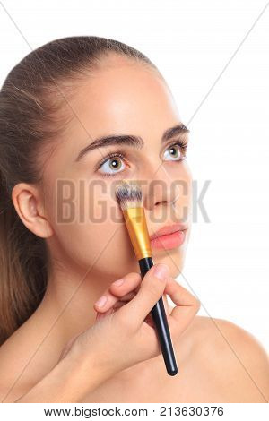 A girl with open eyes put a foundation cream brush under the eyes on a white isolated background