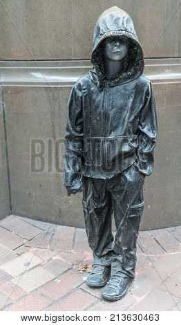 Sydney Australia - March 25 2017: Closeup of diminutive bronze statue of youngster with hoodie on corner of George and Barrack Streets represents child refugees and project shame on Australian Government.