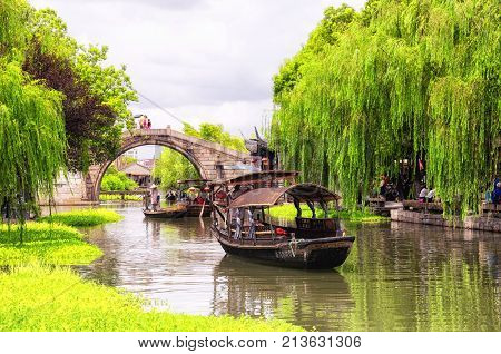 August 8 2015. Xitang Town China. Wolong bridge and tourist boats on the water canals of Xitang old town located in in Jiashan County in Jiaxing City Zhejiang Province china.