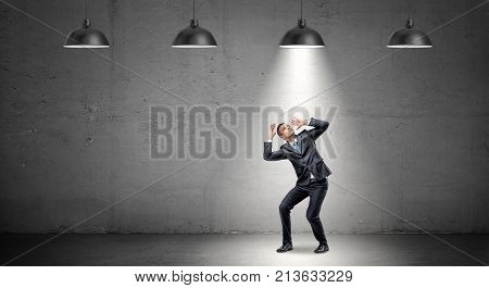 A scared businessman stands cowering under the rays of industrial pendant lights right above him. Shadow business. Found culprit. Caught in the act.