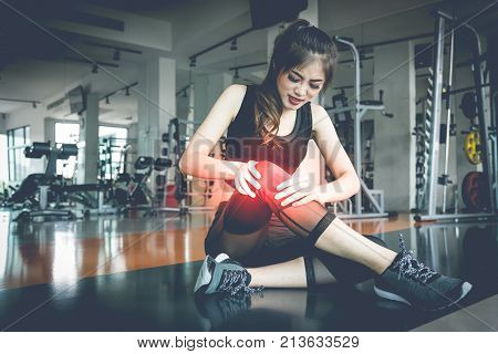 Asian woman injuries during workout at knee in fitness gym. Medical and Healthcare concept. Exercise and Training theme.