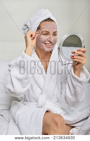 Attractive woman wearing a face mask beauty treatment holding a mirror as she plucks her eyebrows with tweezers