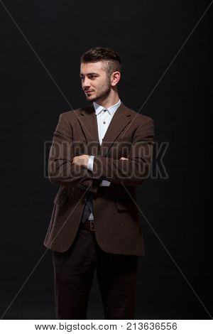 A stylish man folded his arms looking away with a slight smile on his chest against a black background