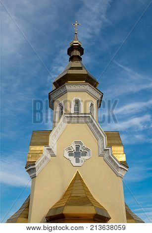 Golden dome of a church against a blue sky and white clouds.