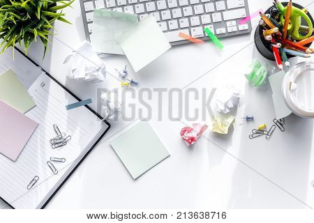 Clutter in office. Desk covered with crumpled paper and scattered stationery. White background top view.