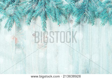 Winter background. Blue fir tree branches with winter snowflakes on the wooden background. Winter still life,free space for text -festive winter background. Winter background with winter fir tree branches, flat lay