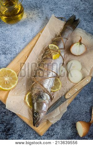 Preparation of fish for baking. Raw zander onions and fresh lemon on a kitchen cutting board on a dark background.