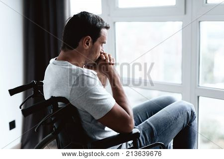 A disabled person in a wheelchair sits in front of a large panoramic window and is sad. He looks out the window. He is in his modern apartment.