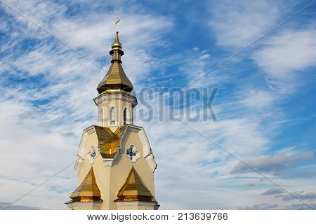 dome of the church against the blue sky and white clouds.