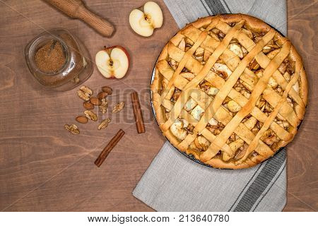 apple pie on a gray kitchen towel, wooden table, with apples, cinnamon, sugar and nuts, top view