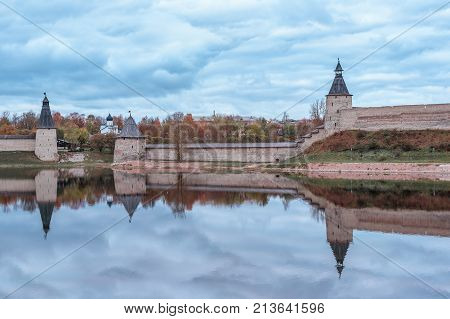 Horizontal shot of Pskov Kremlin and cloudy sky reflecting in the river on autumn evening