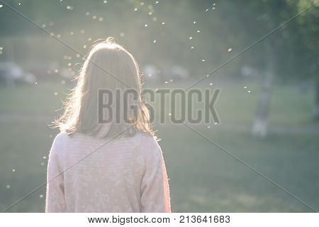 Horizontal shot in soft focus of rear view of standing girl, a teenager thinks, insects flying over his head as thoughts