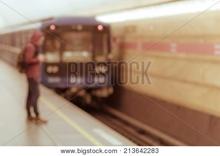 The blur shot of young man in casual clothes with gadget in hand waiting for the metro train