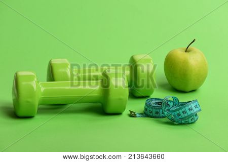 Dumbbells In Bright Green Color, Twisted Measure Tape And Fruit