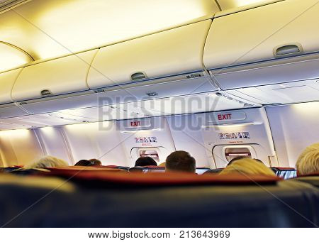 Passenger seat, Interior of airplane with passengers sitting on seats. Travel concept, vintage color, selective focus.