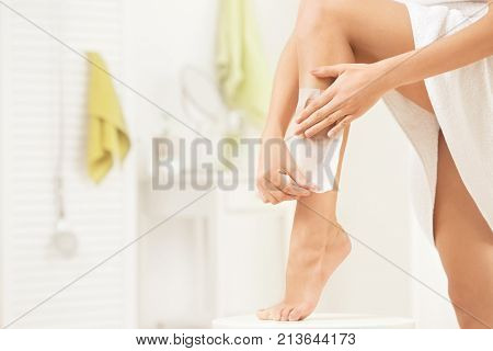 Young woman depilating her leg with wax stripe at home
