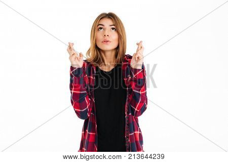 Image of hopeful young woman standing isolated over white wall background. Looking aside gesturing with fingers.